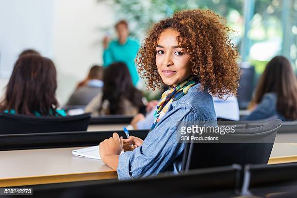 Pretty curly haired high school or college girl in classroom