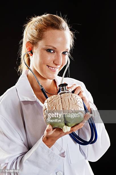 Pretty doctor smiles as she uses stethoscope on model brain