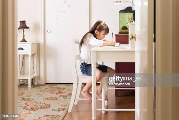 Pretty Eurasian girl doing homework in her bedroom