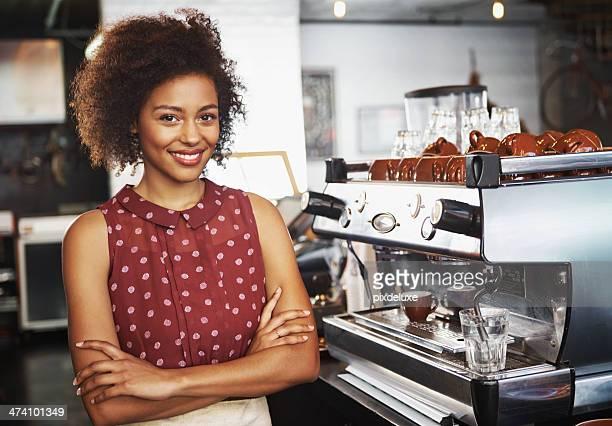 Hübsche barista lächelnd Frau hinter der Theke