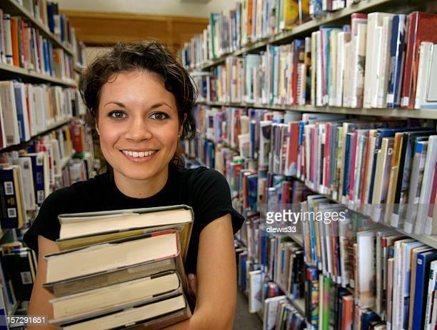 Pretty female student posing in library with stacks of books