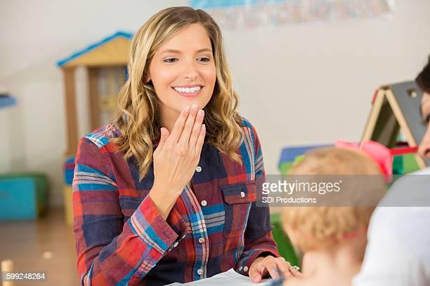 Pretty female teacher using sign language to speak to preschooler