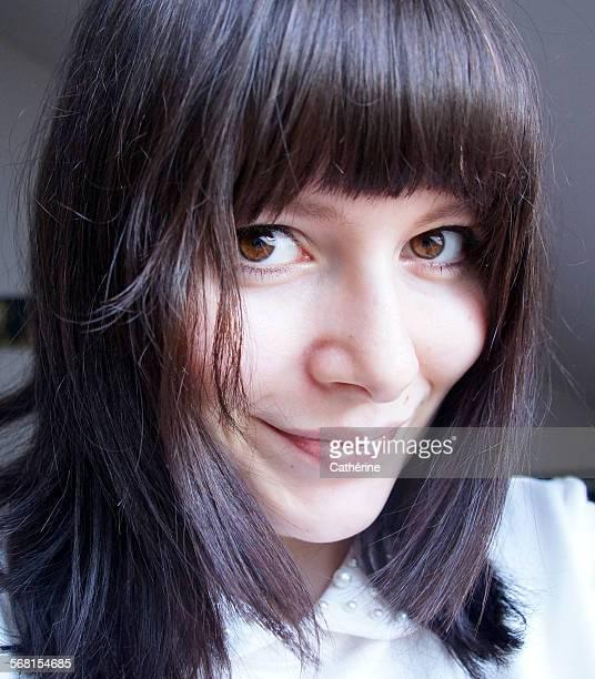 Pretty female with dark, sleek hair and fringe