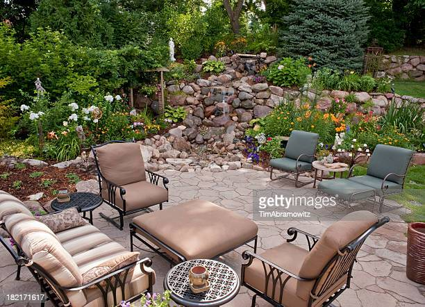 Pretty garden patio with stone fountain and seating