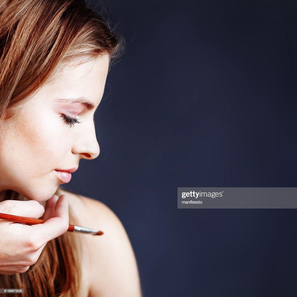 pretty girl applying make up by makeup artist : Stock Photo