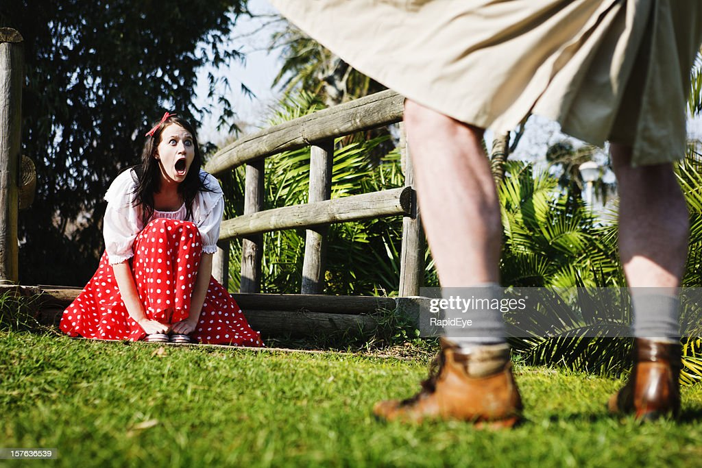 Pretty girl gapes, shocked, as flasher exposes himself in park : Stock Photo