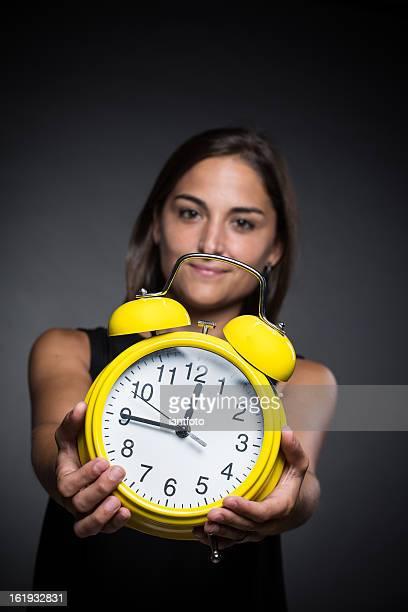 Pretty girl holding a yellow clock