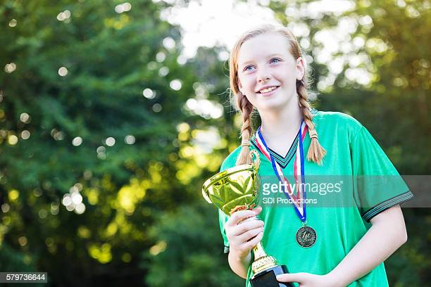 Pretty girl holding up the winning soccer trophy