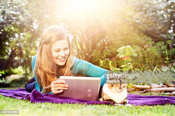 Jolie fille dans le jardin avec ordinateur portable et des clients contents chat