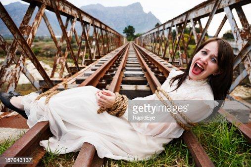 Pretty girl in period dress tied to railroad bridge, screaming