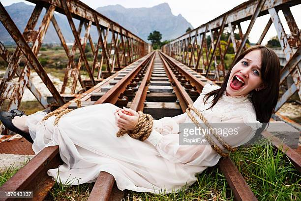Pretty girl in period dress tied to railroad bridge, screaming
