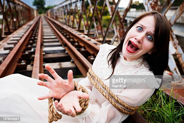 Pretty girl in Victorian dress tied to railroad. High drama!