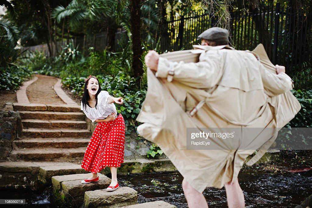 Pretty girl laughs and points mockingly at flasher in park : Stock Photo