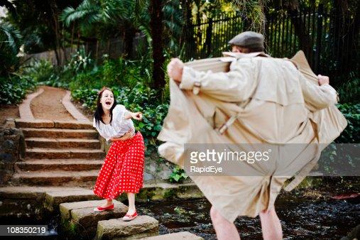 Bonita Menina gargalhadas e pontos mockingly em exibicionista sexual no parque : Foto de stock