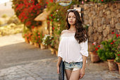 Beautiful stylish girl walking on a street with pavement in old town. Travel concept.