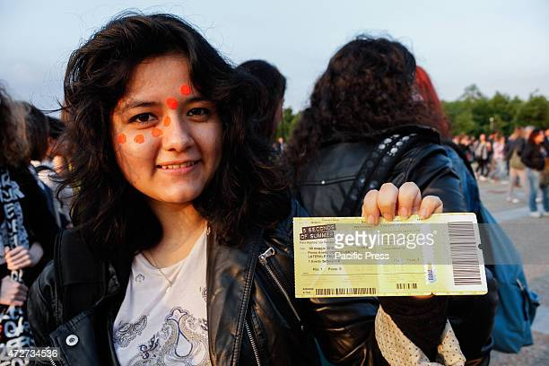 A pretty girl shows the ticket of the first Italian concert date of Australian pop band called 5 Seconds of Summer