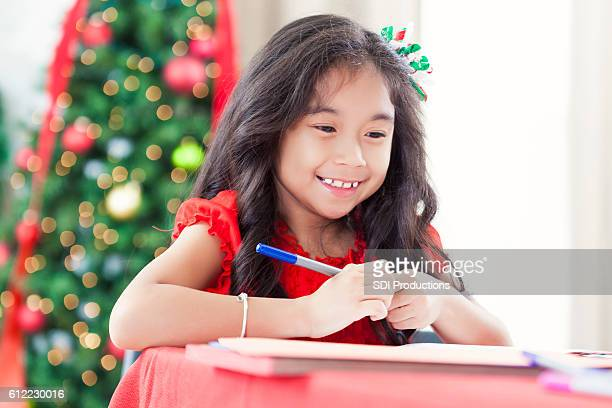 Pretty girl smiles whilte making homemade Christmas card