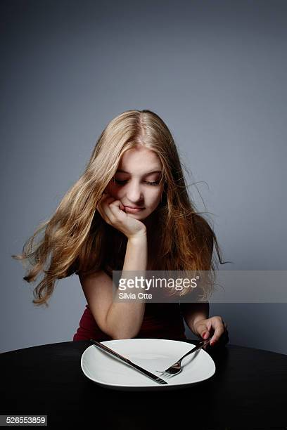 Pretty girl staring at empty plate