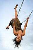 Pretty girl upside down on swing sticking tongue o