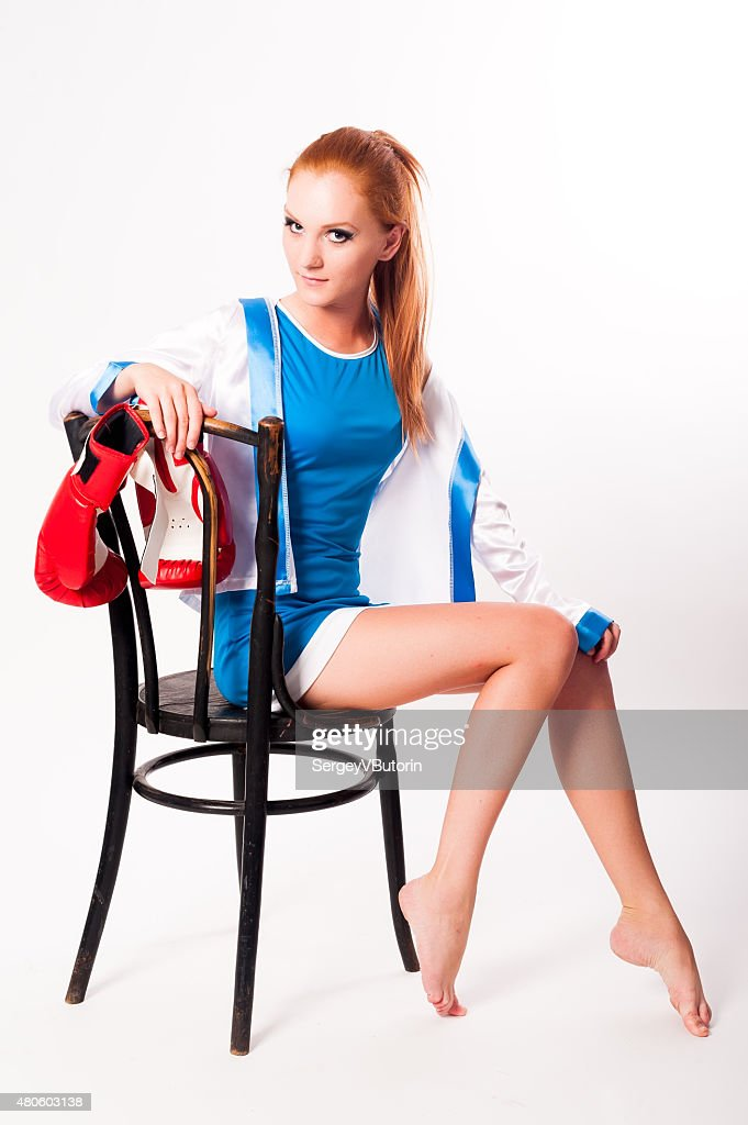 Pretty girl with boxing gloves on chair : Stock Photo