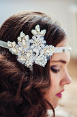 Pretty girl with handmade floral headband. Professional make-up and hairstyle. Perfect skin. Fashion photo. Gatsby style.