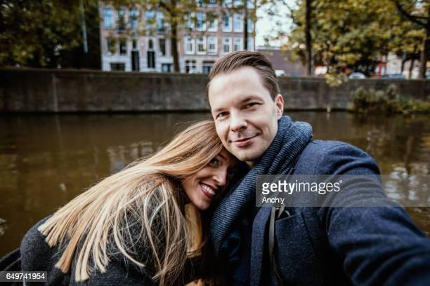 Jolie fille aux cheveux longs se penche sur l'épaule de son copain. Jeune homme prenant selfie de lui et sa copine sur le quai
