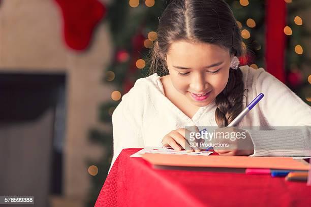 Pretty girl writing in a Christmas card to Santa