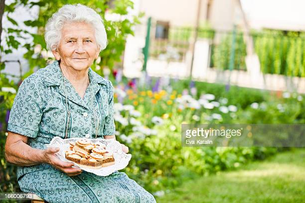 Pretty grandmother holding a plate full of cakes