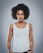 Centered front view of gorgeous young woman wearing white sleeveless undershirt and calm expression with thumbs in pockets over gray background