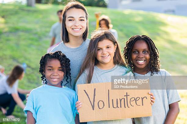 Pretty group of young girl volunteers holding sign