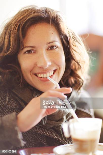 Pretty happy woman drinking coffee with straw