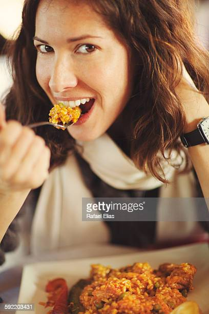 Pretty happy woman eating paella