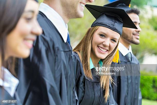 Pretty high school graduate smiling before receiving diploma