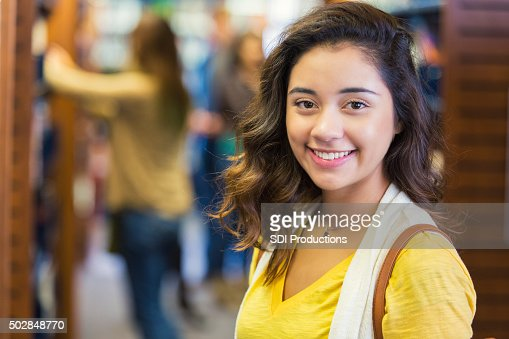Pretty high school or college student stands in school library