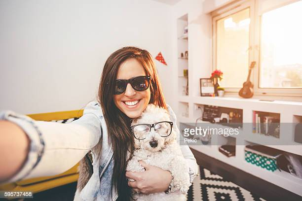 Pretty hipster girl taking selfie with her funny dog