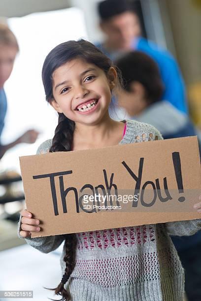 Jolie hispanique enfant tenant Merci ! Inscrivez à la banque alimentaire