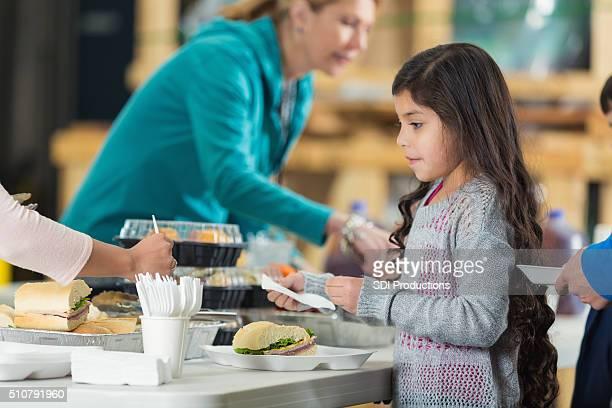 Pretty Hispanic girl in line at soup kitchen