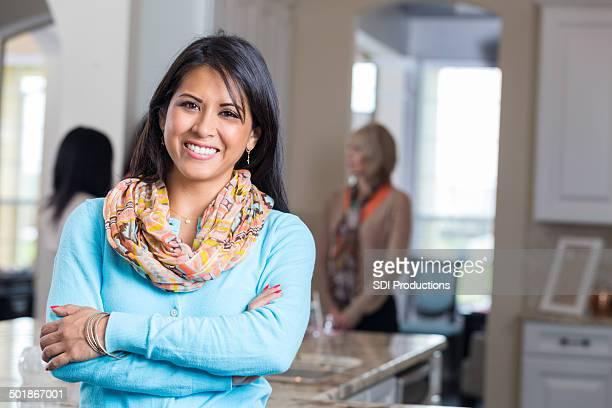 Pretty Hispanic woman hosting direct sales fashion party at home