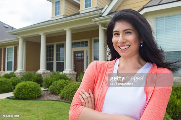 Pretty Hispanic Woman standing in front of newly purchased home