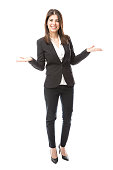 Full length portrait of a beautiful young woman in a suit working as a hostess and greeting people with a smile