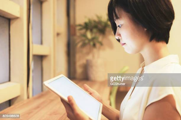 Pretty Japanese lady using a digital tablet