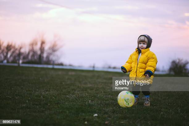 Pretty Kid Playing Soccer On Autumn Day