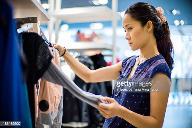 Pretty lady choosing clothes in department store