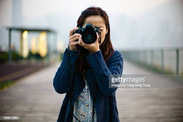 Pretty lady holding & shooting with pro SLR camera