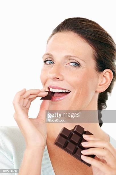 A pretty lady putting a piece of dark chocolate in her mouth