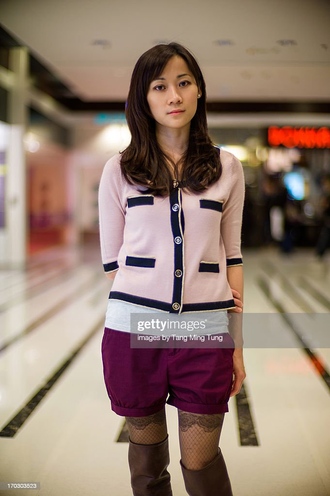 Pretty lady standing & looking into camera in mall : Stock Photo