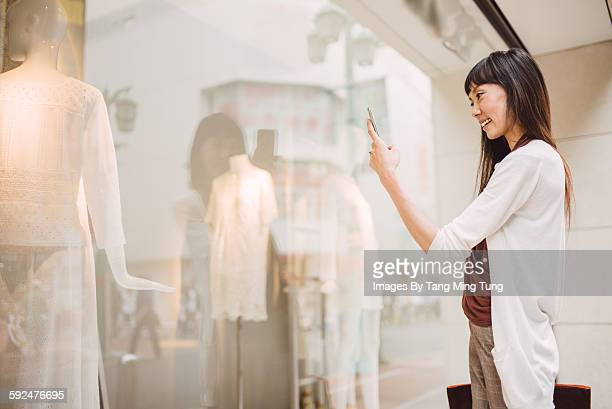 Pretty lady talking a picture at window display