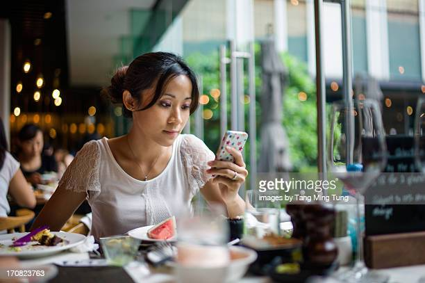 Pretty lady using smartphone after finished lunch
