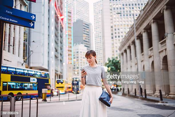 Pretty lady using smartphone in business district