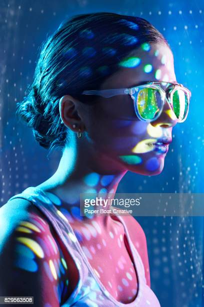Pretty lady wearing sunglasses with blue circular shadows and spots reflected on her